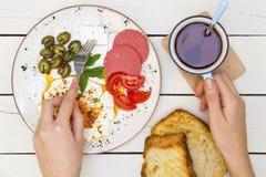 Mulher que come o café da manhã saboroso na manhã foto de stock