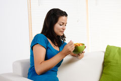 Mulher que come o cereal de pequeno almoço Foto de Stock Royalty Free
