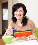 Mulher que come o cereal em casa fotografia de stock royalty free