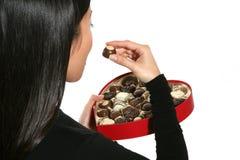 Mulher que come o chocolate dos Valentim foto de stock