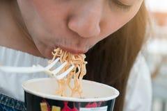 Mulher que come o copo dos macarronetes com uma forquilha plástica Fotografia de Stock