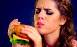 Mulher que come o fast food Menina que aprecia o Hamburger delicioso fotos de stock