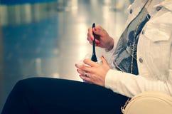 Mulher que come o fruto de um vidro do plástico, esperando um avião em um aeroporto imagem de stock