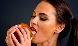 Mulher que come o Hamburger A menina quer comer o fast food imagens de stock royalty free