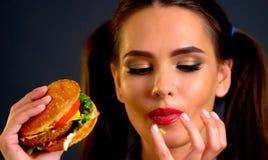 Mulher que come o Hamburger A menina quer comer o fast food imagens de stock