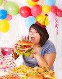 Mulher que come o Hamburger no aniversário. Fotos de Stock