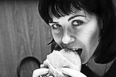 Mulher que come o hamburguer Fotografia de Stock Royalty Free