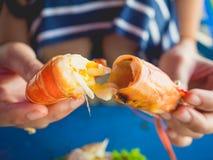 A mulher que come o local grelhou o marisco da praia de Tailândia imagens de stock