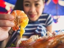 A mulher que come o local grelhou o marisco da praia de Tailândia imagem de stock royalty free