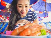A mulher que come o local grelhou o marisco da praia de Tailândia fotografia de stock royalty free