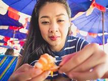 A mulher que come o local grelhou o marisco da praia de Tailândia fotos de stock