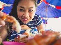 A mulher que come o local grelhou o marisco da praia de Tailândia foto de stock royalty free