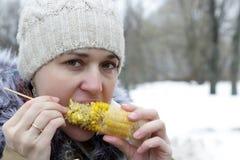 Mulher que come o milho Imagens de Stock Royalty Free