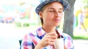 Mulher que come o milho do alimento da rua no parque do verão, conceito do alimento do curso video estoque