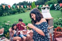 Mulher que come o pedaço de bolo no partido do verão Imagem de Stock