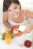 Mulher que come o pequeno almoço na cama Fotografia de Stock