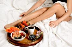 Mulher que come o pequeno almoço na cama Imagem de Stock