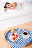 Mulher que come o pequeno almoço caseiro encontrar-se na cama Imagem de Stock