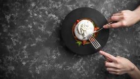 A mulher que come o queijo do burrata na placa de madeira pequena serviu com tomates e manjericão frescos no fundo textured escur fotografia de stock royalty free