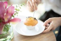 Mulher que come o queque no café imagens de stock royalty free