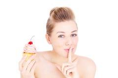 Mulher que come o queque no segredo Fotografia de Stock