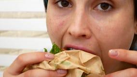Mulher que come o sanduíche, assentando perto da janela no café vídeos de arquivo