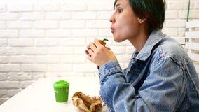 Mulher que come o sanduíche, assentando perto da janela no café video estoque