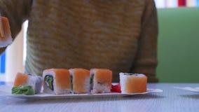 Mulher que come o sushi de uma placa em um restaurante japonês Tiro da zorra video estoque