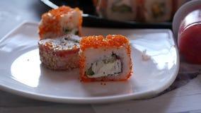Mulher que come o sushi na culinária japonesa do restaurante, hashis dos usos o close-up rola o movimento lento filme