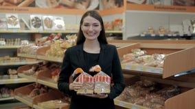 Mulher que come os pães, morena feliz no supermercado da loja com pão do brinde Fotografia de Stock