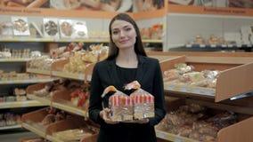 Mulher que come os pães, morena feliz no supermercado da loja com pão do brinde Fotografia de Stock Royalty Free
