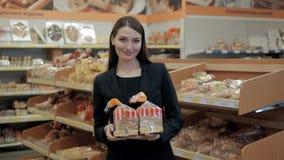 Mulher que come os pães, morena feliz no supermercado da loja com pão do brinde Foto de Stock Royalty Free