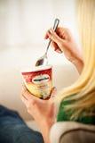 Mulher que come a pinta do creme de Haagen-Dazs Vanilla Ice Fotografia de Stock Royalty Free