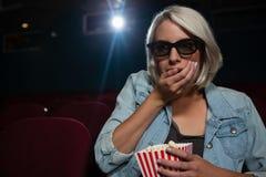 Mulher que come a pipoca ao olhar o filme no teatro imagem de stock