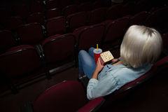 Mulher que come a pipoca ao olhar o filme no teatro foto de stock royalty free