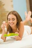 Mulher que come a salada em casa Imagem de Stock