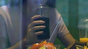 Mulher que come a salada fresca e que bebe a bebida carbonatada doce, apego do açúcar vídeos de arquivo