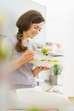 Mulher que come a salada fresca na cozinha imagens de stock royalty free