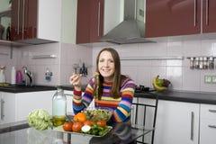 Mulher que come a salada no kithen Fotografia de Stock