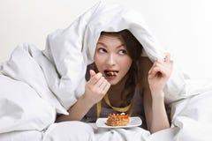 Mulher que come sob a tampa Fotografia de Stock