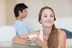Mulher que come um chá quando seu noivo se sentar em um sofá foto de stock royalty free