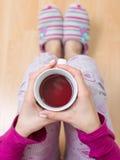 Mulher que come um copo do chá Fotografia de Stock