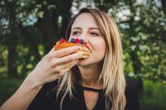 Mulher que come um pice com cobertura em chocolate do mirtilo e da framboesa do bolo imagem de stock