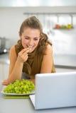 Mulher que come a uva na cozinha e que usa o portátil Imagem de Stock