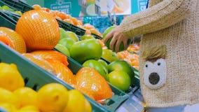 Mulher que compra citrinas exóticas frescas na mercearia imagem de stock royalty free
