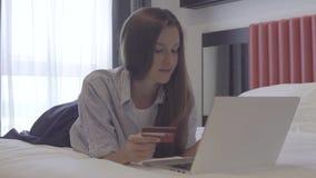 Mulher que compra em linha com seu portátil, mentira na cama filme