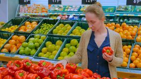 Mulher que compra pimentos de sino vermelhos frescos na mercearia fotos de stock