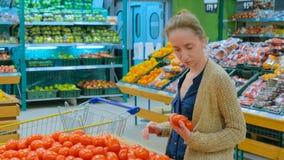 Mulher que compra tomates vermelhos frescos na mercearia fotos de stock royalty free