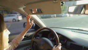 Mulher que conduz o automóvel e que estende a viseira de sol transporte excitador video estoque