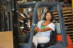 Mulher que conduz o caminhão de empilhadeira no armazém Foto de Stock